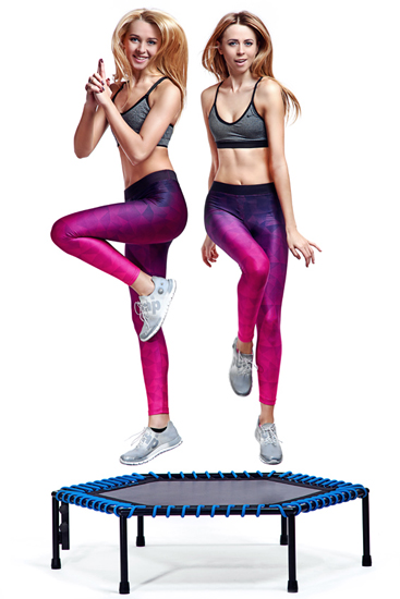 Dwie wysportowane dziewczyny skaczące na trampolinie