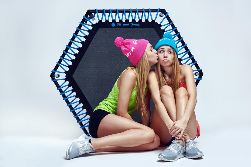 Dziewczyny w sportowym stroju siedzą na tle trampoliny.