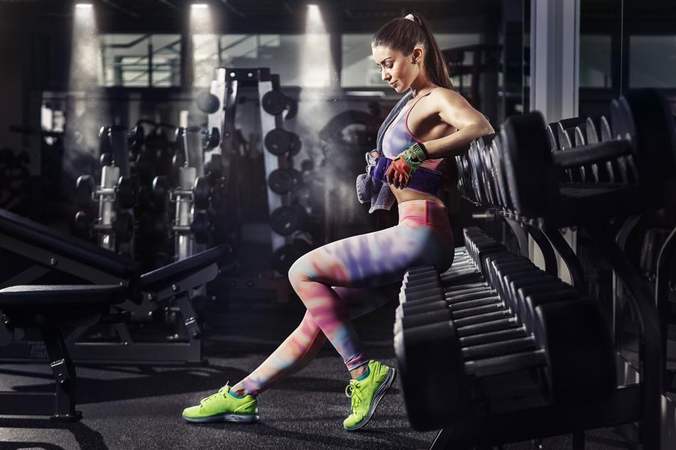 Wysportowana dziewczyna w kolorowym stroju fitness, przygotowuje się do treningu na siłowni.