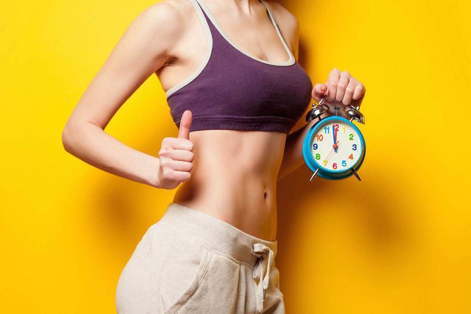 Wysportowana kobieta na żółtym tle trzymająca kolorowy zegar.