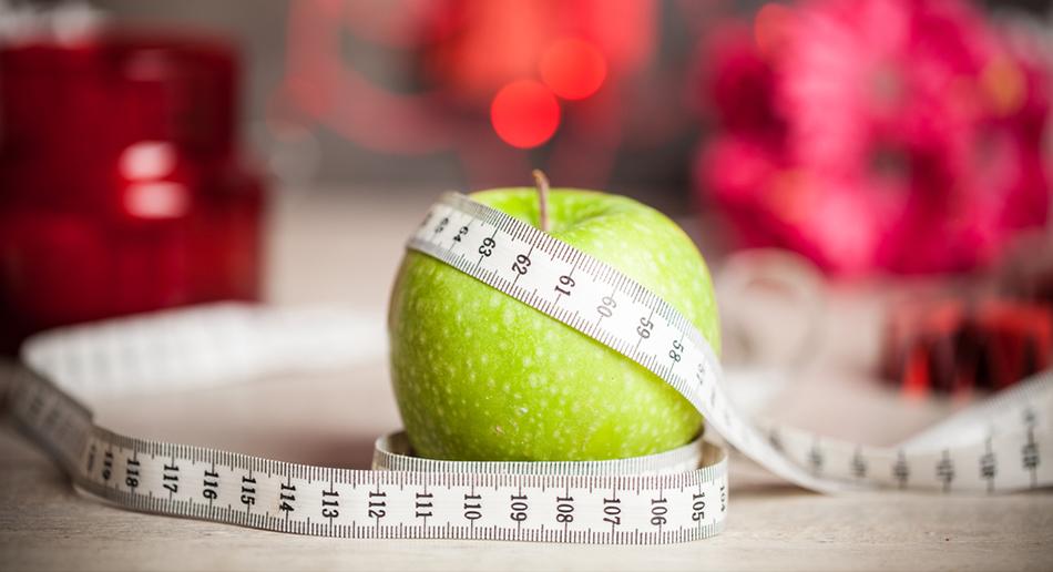 Zielone jabłko owinięte miarką do mierzenia obwodu ciała.